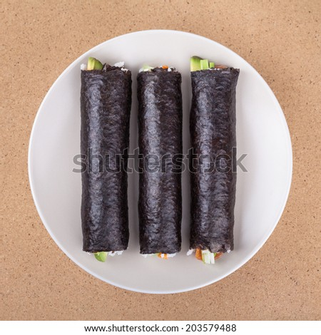 Three Sushi rolls wrapped in Nori seaweed on plate, over wooden background. - stock photo