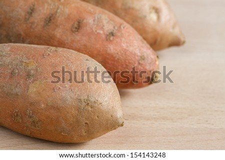 Three sweet potatoes on a wooden chopping board - stock photo