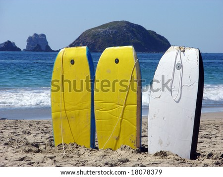 Three swimming boards for rent on Playa del Palmas beach in Ixtapa resort town, Mexico. - stock photo