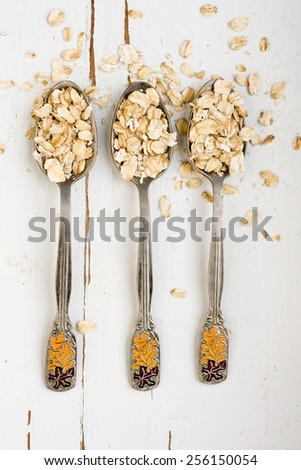 Three tablespoons of oatmeal lying on a white wooden background. Healthy food. - stock photo