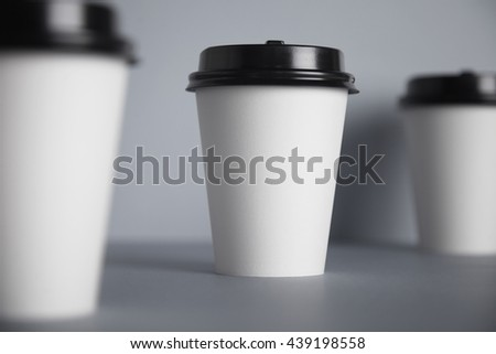 Three take away white paper cups with closed black caps, top view, isolated on simple gray background, central cup in close focus, cups aside are unfocused in bokeh - stock photo