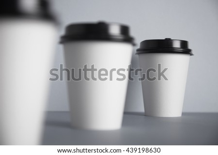 Three take away white paper cups with closed black caps, top view, isolated on simple gray background, last cup in close focus, cups ahead are unfocused in bokeh - stock photo
