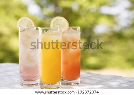 Three tall glasses filled with assorted beverages and ice. - stock photo