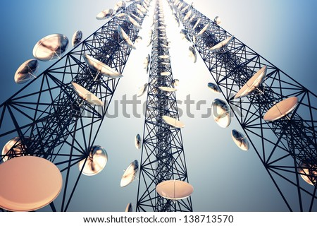 Three tall telecommunication towers with antennas on blue sky. View from the bottom. - stock photo