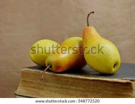 Three tasty ripe autumn pears on an old book. - stock photo