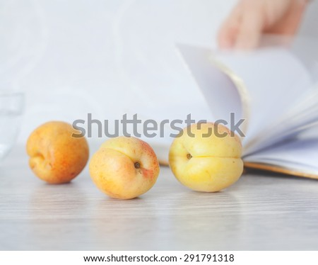 Three tasty ripe orange apricots on a table against background of open book - stock photo