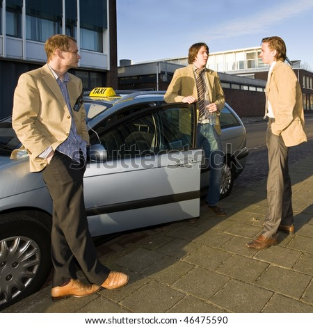 Three taxi drivers hanging around a cab during their break - stock photo