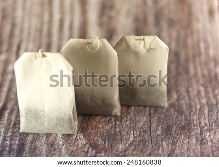 Three tea bags in raw on wooden background - stock photo
