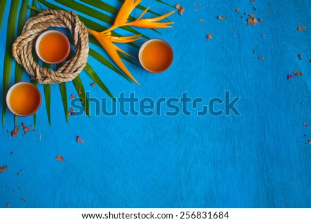 three teacups with shuck, coil of rope, green leaves and yellow flower on blue wooden background. Top view.  - stock photo