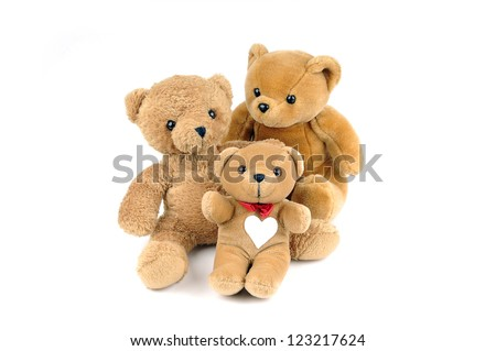 Three teddy bears, one has a patch in the shape of a heart on the chest - stock photo