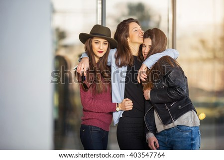 Three teen girl friends laughing. Selective focus - stock photo