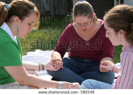 Three teen girls gathered outdoors to pray. - stock photo