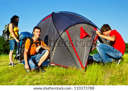 Three teenage backpackers beside camping tent - stock photo