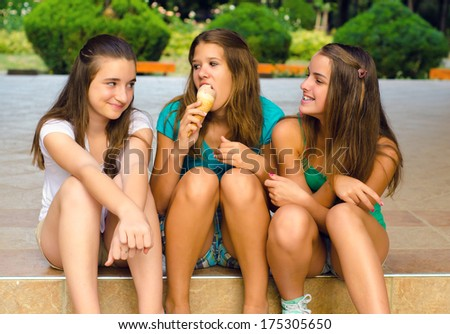 Three teenage friends and one ice cream on beautiful summer day.