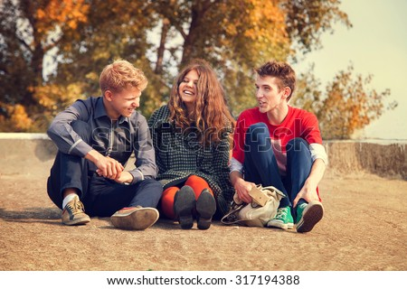 Three teenage friends have a fun time in golden autumn day - stock photo
