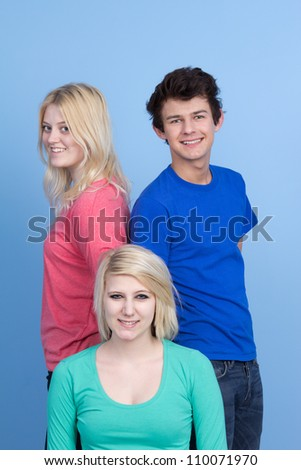 Three teenage friends standing together against a blue backing