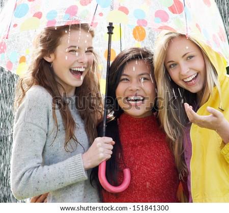 Three Teenage Girl Sheltering From Rain Beneath Umbrella - stock photo