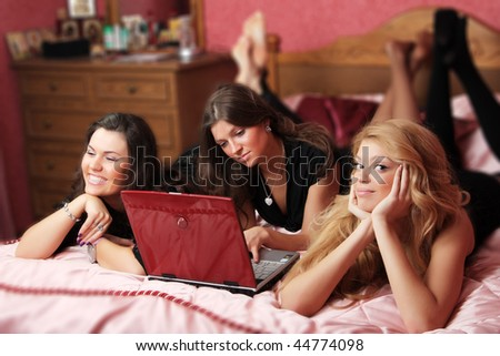 three teenage girls having fun with a laptop on the bed - stock photo