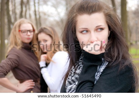 Three teenage girls in emotional scene in the park - stock photo