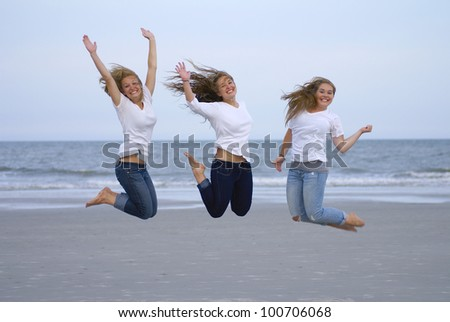 Three teenage girls jumping for joy at the beach - stock photo