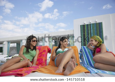 Three teenage girls lying on sunloungers at resort - stock photo