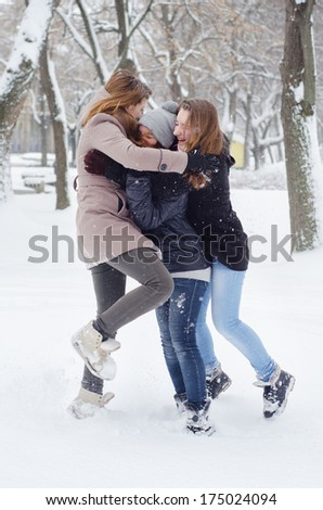 Three teenage girls playing in the snow on cold winter day.