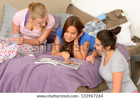 Three teenage girls reading at slumber party in pajamas - stock photo