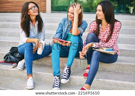 Three teenage girls talking on school steps - stock photo