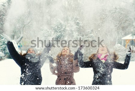 Three teenage girls throwing snow in the air. - stock photo