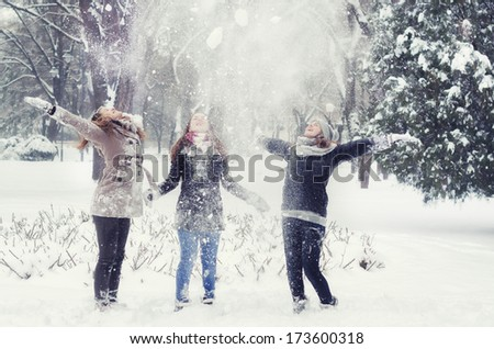 Three teenage girls throwing snow in the air on cold winter day. - stock photo