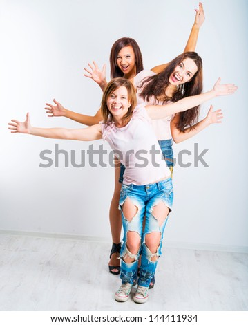 three teenage girls with hands up on light background