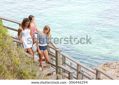 Three teenager girls arriving at beach, walking down a wooden path with steps smiling, with clear sea background on a summer holiday together, beach exterior. Adolescents travel lifestyle outdoors. - stock photo