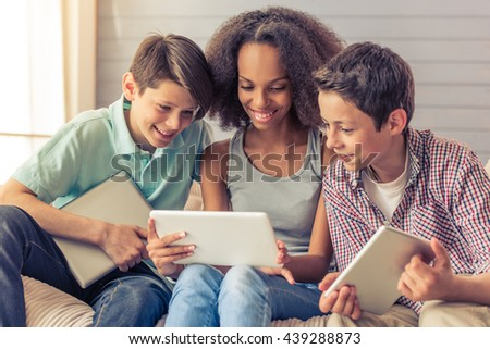 Three teenagers are using tablets and smiling while sitting on the couch at home. Attractive afro american girl is sitting between boys