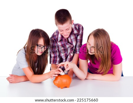 Three teenagers collecting money together for their future business. They put coins in piggy bank - stock photo