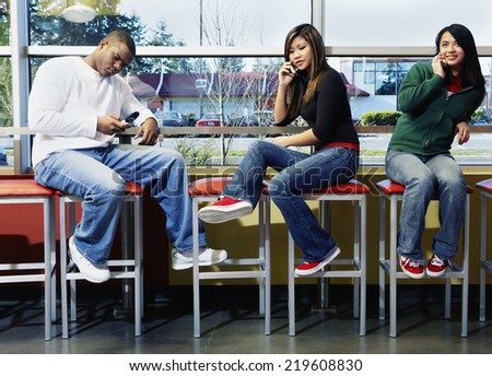 Three teenagers on stools with cell phones - stock photo