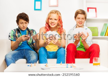 Three teenagers playing table game on white sofa - stock photo