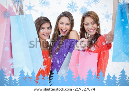 Three teenagers raising their arms while holding their purchases against snowflakes and fir trees in blue - stock photo