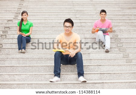 Three teenagers sitting on staircase - stock photo