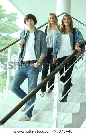 Three teenagers walking down stairs - stock photo