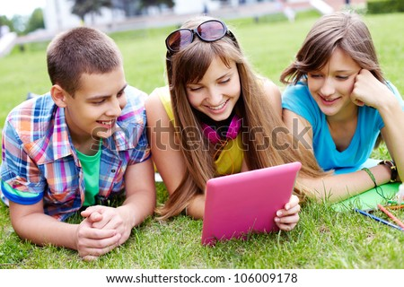 Three teens looking at the screen of the digital pad and smiling - stock photo