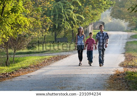 Three teens walking with holding hands on country road at sunset