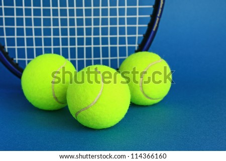 Three tennis balls and racket on blue background.