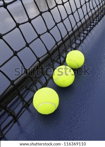 Three tennis balls by net on wet court after rain - stock photo