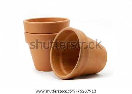 Three terracotta plant pots on a white background. - stock photo