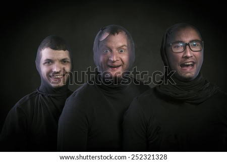 Three thieves in balaclavas on their faces, dressed in black. Studio shot on black background. - stock photo