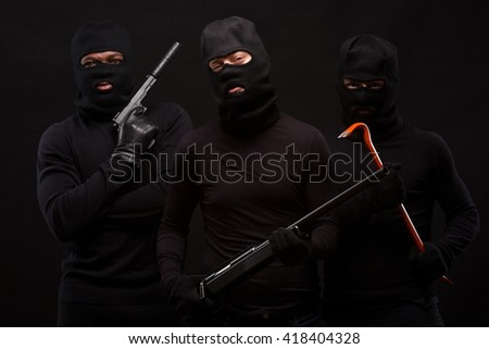 Three thieves in balaclavas on their faces, dressed in black. Studio shot on black background. Men holding weapons: guns, rifles, etc. Isolated on black. - stock photo