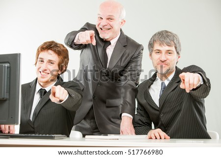 three thrilled businessmen or sales men pointing out to you