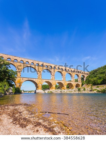 Three-tiered aqueduct Pont du Gard - the highest in Europe. The bridge was built in Roman times on the river Gardon. Provence, spring sunny day - stock photo