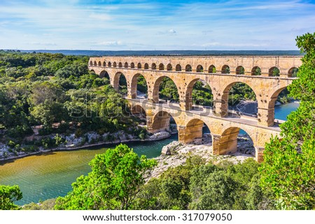 Three-tiered aqueduct Pont du Gard was built in Roman times on the river Gardon. Around the bridge is magnificent natural park. Provence, spring sunny day - stock photo