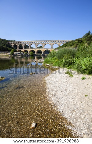 Three-tiered aqueduct Pont du Gard was built in Roman times on the river Gardon - France - stock photo